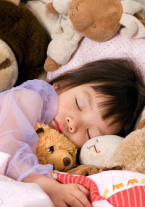 child asleep with lots of teddies